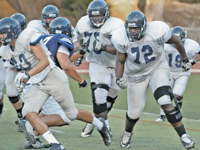 College of the Canyons offensive linemen Tyler Phillips (75) and Lloyd Tunstill (72) block in practice on Wednesday.