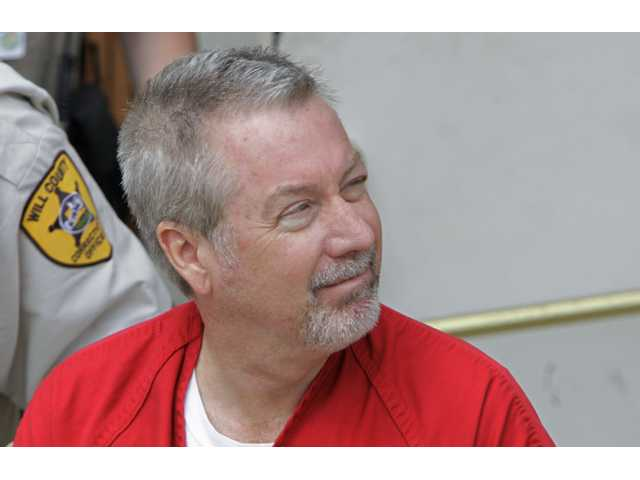 In this May 8, 2009 file photo, former Bolingbrook, Ill., police officer Drew Peterson leaves the Will County Courthouse in Joliet, Ill., after his arraignment on charges of first-degree murder in the 2004 death of his third wife, Kathleen Savio.