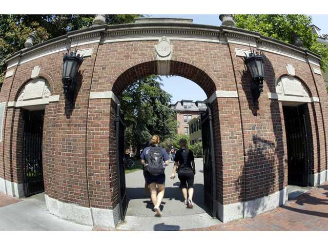 Pedestrians walk through a gate on the campus of Harvard University, where dozens of students are being investigated for cheating.