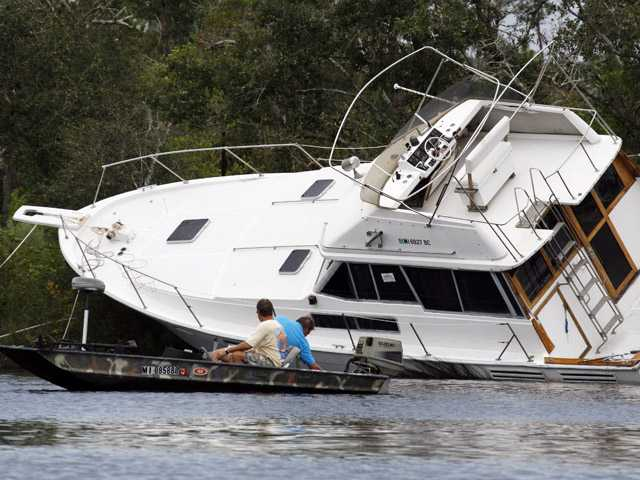 Several men try to free this grounded yacht on Twin Lake, near Diamondhead, Miss., Friday.