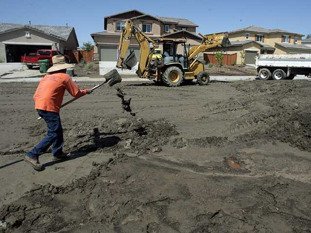 Workers remove mud from Landon Drive at Dover Dr. in Moreno Valley, Calif., on Friday, after the neighborhood flooded Thursday from sudden rain storms.