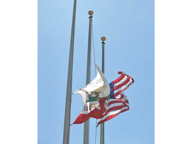 The American flag and California flag fly at half-staff at Valencia High School in honor of Armstrong on Friday.