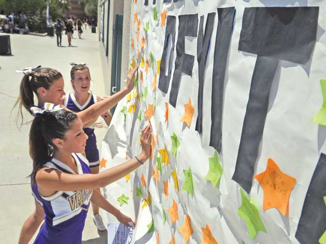 Cheerleaders from front, Megan Arima, Audrey Hixon and McCall Honaker place drug-free pledge stickers on a poster at the DFYiT kickoff event held at Valencia High School on Friday.