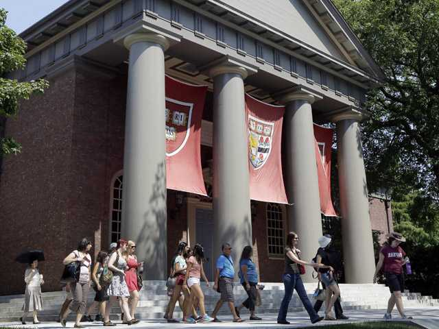 People are led on a tour group at the campus of Harvard University in Cambridge, Mass., on  Thursday.