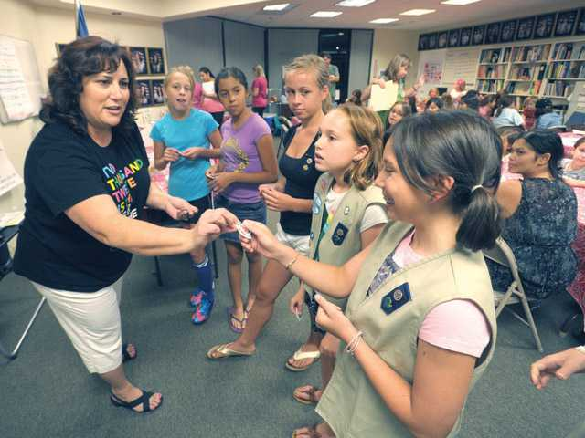 Irma Tamayo, Girl Scouts of Los Angeles mission delivery specialist of membership, left, hands out patches to the Girl Scouts who helped out at the Girl Scout Ice Cream Social and Registration Night held at the Santa Clarita Service Center on Thursday.