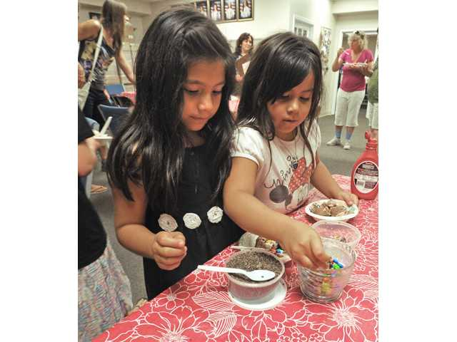 Seven-year-olds Emily, left, and Jazzlynn Herrera choose ice cream toppings at the Girl Scout Ice Cream Social and Registration Night held at the Santa Clarita Service Center on Thursday. (Above) A group of girls who registerd to become Girl Scouts look at photos of Girl Scout Gold Award honorees.