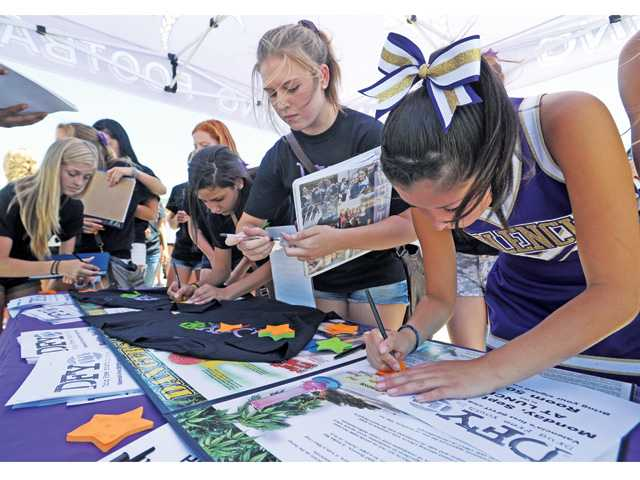 Students sign their names on pledge-to-be-drug-free stickers at the DFYiT anti-drug kickoff event held at Valencia High School on Friday.
