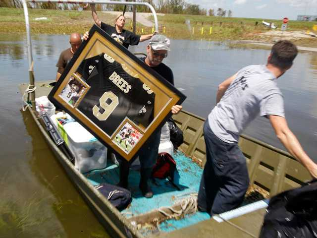 Russell Wilson unloads a water damaged Drew Brees signed shirt for his daughter Amy Keller and her husband Michael from their Braithwaite, La. home, Saturday.