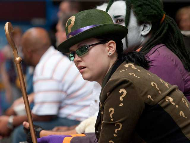 Christina Barton, of Douglasville, Ga., watches fellow attendees walk along the sidewalk at Dragon Con in Atlanta, on Friday.