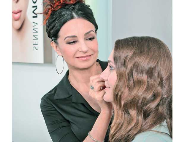Eugenia Weston applies makeup to a customer at Senna Costmetics.