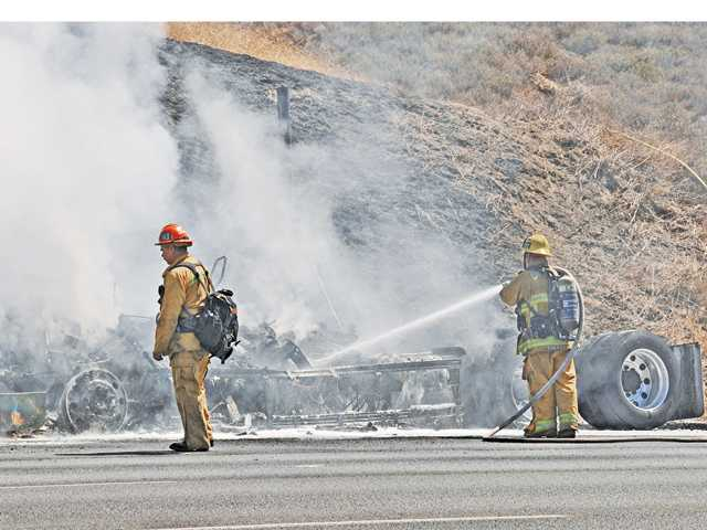 Firefighters water down the wreckage of a big rig on the northbound Interstate 5 north of Templin Highway on Sunday.