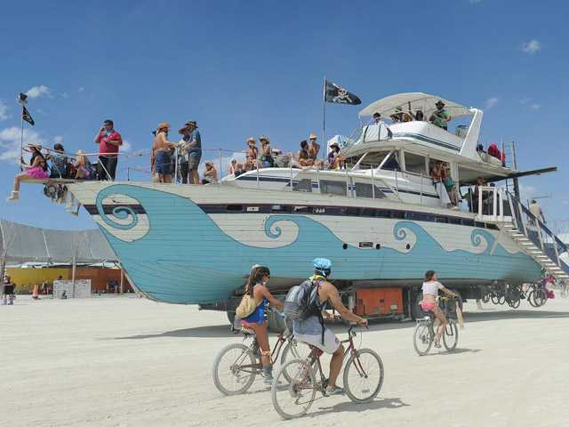 An old wooden yacht art car rolls through the playa at Burning Man on the Black Rock Desert near Gerlach, Nev. on Friday.