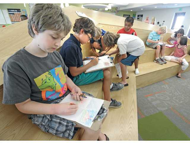 From left, fifth-graders Austin Horner, and Leo Melaye draw their thoughts when listening to music at Santa Clarita Valley International Charter School in Castaic on Thursday.