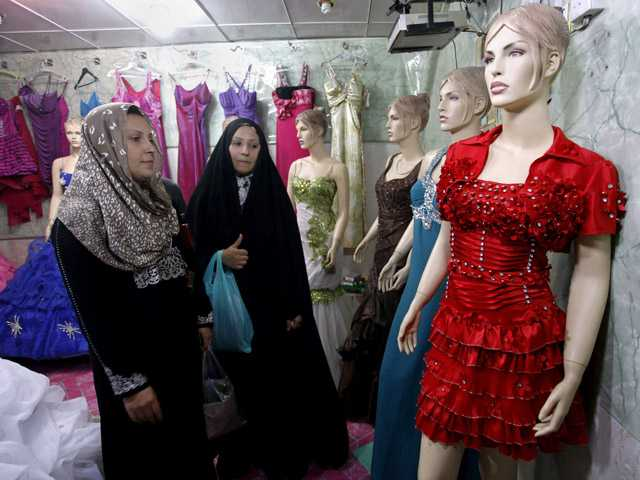 In this Sunday photo, Iraqi women shop at a women's fashion store in Diwaniyah, 80 miles south of Baghdad, Iraq, on Sunday.