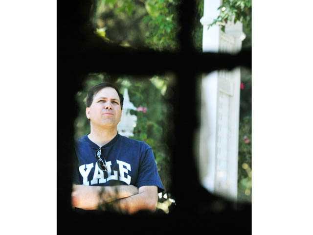Maurice Oillataguerre, brother of homeowner Peter Oillataguerre, is seen through a charred window frame as he looks at the façade of his brother's fire-damaged home. Jonathan Pobre/The Signal