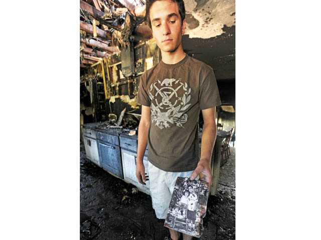 Ryan Oillataguerre shows an old photograph of himself and his younger sister Ashley as his family sifts through belongings following a house fire in Newhall on Monday. Jonathan Pobre/The Signal