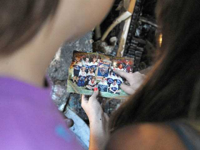 Maddy Anderson, left, and Ashley Oillataguerre recover a photo amid the charred remains of the family room. Jonathan Pobre/The Signal