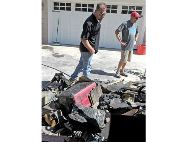 Family members Todd Hall, left, and Mike Anderson look through charred belongings behind Peter Oillataguerre's home in Newhall on Monday. Jonathan Pobre/The Signal