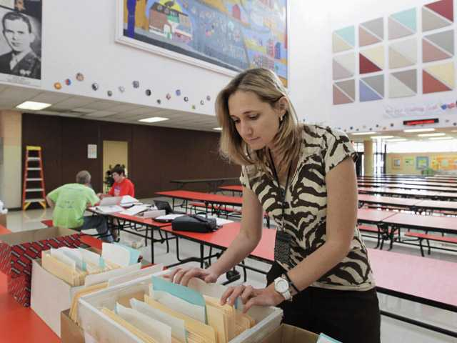 Vicky Kleros, principal of the Manuel Perez Jr. Elementary School in Chicago's predominantly Hispanic Pilsen neighborhood, looks through files at the school.