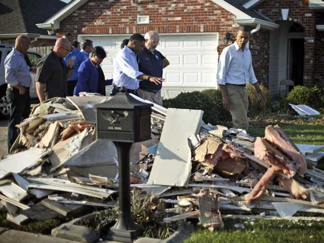 President Barack Obama walks past debris on the sidewalks as he tours the Bridgewood neighborhood in LaPlace, La., on Monday.