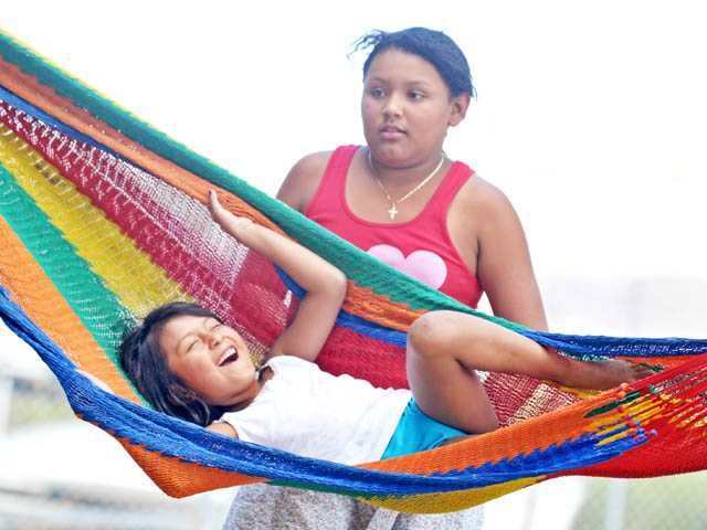 Natalie Cruz, 7, enjoys a moment in a hammock as she and sister Joana Cruz, 11, spend the day at Castaic Lake on Monday.