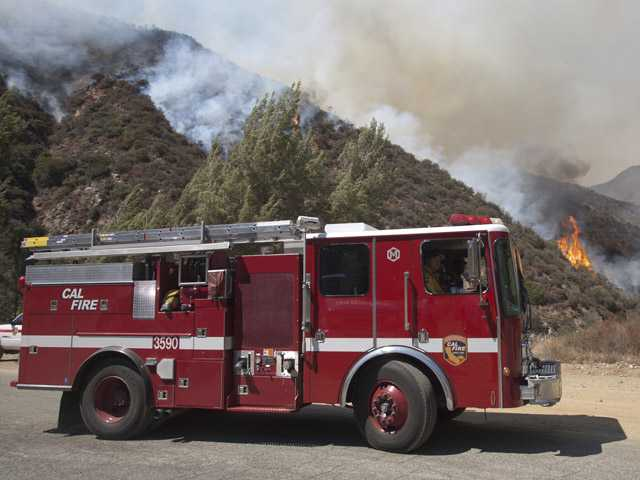 A fire engine pulls away as firefighters fight a wildfire in the Angeles National Forest north of Glendora on Monday.