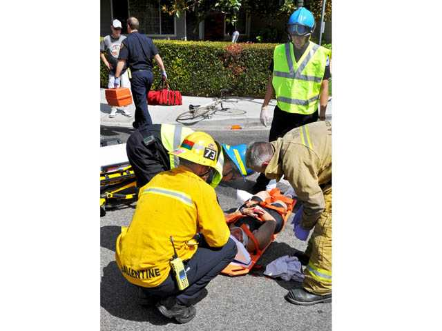 Firefighter/paramedics treat a 55-year-old female bicyclist after she was struck by a hit-and-run driver at Orchard Village Road and Dalbey Drive in Newhall late Tuesday morning. Photo by Rick McClure/For The Signal