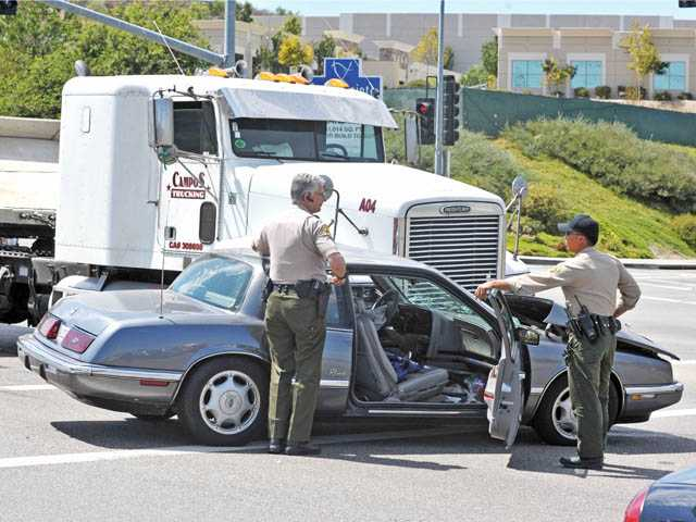 Sheriff's deputies investigate a traffic collision between a tractor trailer and a Buick Riviera at Golden Valley Road and Centre Pointe Parkway in Santa Clarita on Tuesday. One male and one female occupant of the Buick were transported to Henry Mayo Newhall Memorial Hospital with minor injuries, said Capt. Chad Hunter of Fire Station 104. The driver of the tractor trailer was not injured, Hunter said.