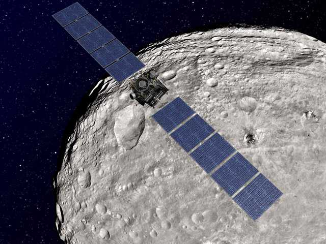 An artist rendering shows the NASA Dawn spacecraft in orbit around the giant asteroid Vesta. Dawn is poised to depart Vesta and head to another asteroid, Ceres, where it will arrive in 2015.