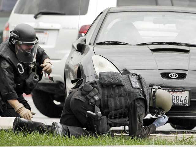 Los Angeles Police bomb squad members check for explosive devices outside a Bank of America branch in Los Angeles on Wednesday.