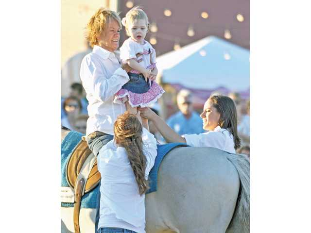 Becky Graham and Madison Drouin, 2, ride Annabelle during the children's demonstration at the 16th annual 'Heart of the West' fundraiser at the Agua Dulce Airport.