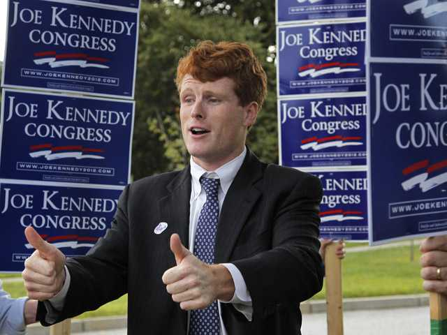Joseph Kennedy III, son of former U.S. Rep. Joseph P. Kennedy II and grandson of the late Robert F. Kennedy gestures while visiting voters outside a polling station at a school in Needham, Mass. on Thursday.