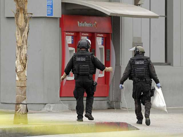 Los Angeles Police bomb squad members check for explosive devices outside a Bank of America branch in Los Angeles Wednesday.