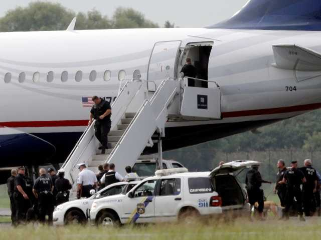 Law enforcement officials work around a US Airways flight at Philadelphia International Airport, after the plane returned to the airport, Thursday when a security scare prompted authorities to recall the airborne flight.