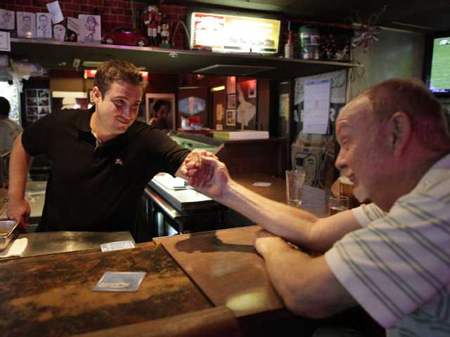 Bar owner Dustin Croick, left, gives a hand to patron Bob Wardsworth, 66, a Vietnam veteran originally from N.Y. at the King Eddy Saloon on Aug. 16.