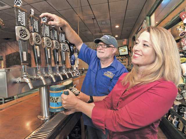 Rob and Laina McFerren serve Wolf Creek beer.
