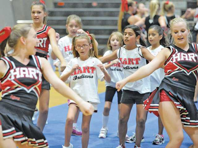 Children learn a routine from Hart High School cheerleaders as they host their annual Spirit Day in Newhall on Saturday.