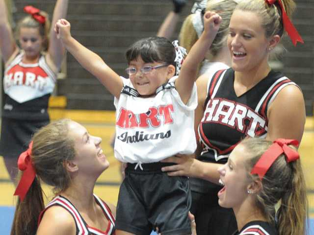 Hart High cheerleaders from left, Jaymee Schienle, Sarah Ratliff, and Jaycee Schienle lift Jayden Fernandez, 4, at the Spirit Day event held at Hart High School on Saturday.