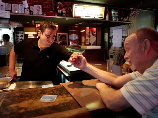 In this photo taken Aug. 16, 2012, bar owner Dustin Croick, left, gives a hand to patron Bob Wardsworth, 66, at the King Eddy Saloon, one of the oldest and most colorful dive bars in Los Angeles.