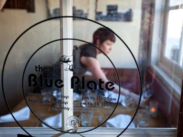A waitress sets a table for dinner at the Blue Plate restaurant in San Francisco. Nearly 200 businesses charge diners an extra fee to pay for employee health care, but millions of dollars of it never gets spent on healthcare.