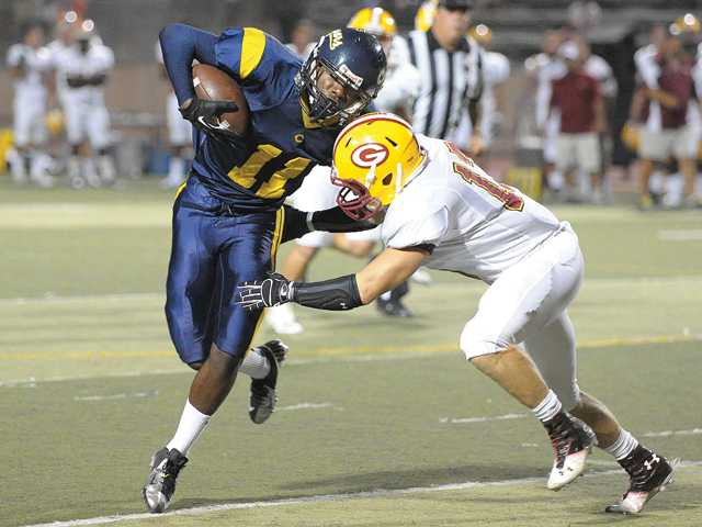 College of the Canyons wide receiver Dijon Barnes, left, fights for yardage during Saturday night's game at COC.