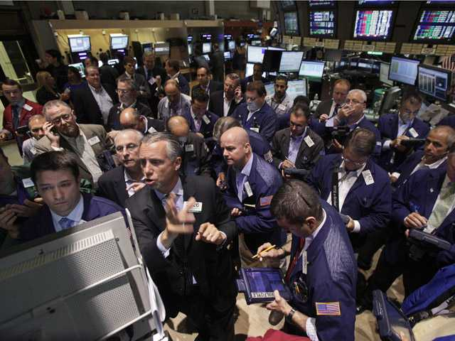 In this Aug. 3 photo, Specialist Donald Himpele, foreground second left, resumes trading in AIG stock on the floor of the New York Stock Exchange.