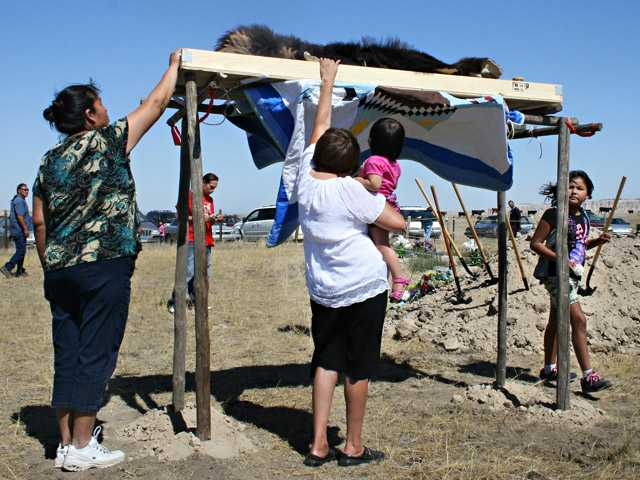 Marlis Afraid of Hawk, center left, touches the buffalo robe wrapped around the remains of her ancestor, Albert Afraid of Hawk, Sunday, in Manderson, S.D.