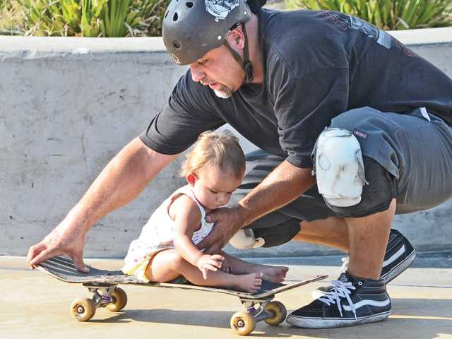 Josh Skweres, gives his daughter Emma a ride on his skateboard at Santa Clarita Skatepark on Monday.