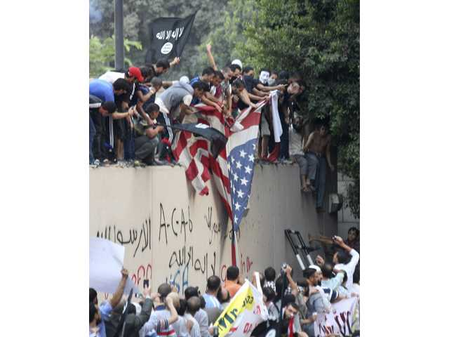 Protesters destroy an American flag pulled down from the U.S. embassy in Cairo, Egypt, Tuesday.