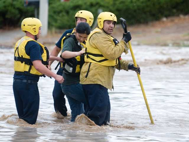 Members of a San Bernardino County Fire Department Swift Water Rescue team pull a woman trapped in the Oro Grande Wash Friday August 17 in Victorville Calif. after a thunderstorm created a flash flood.