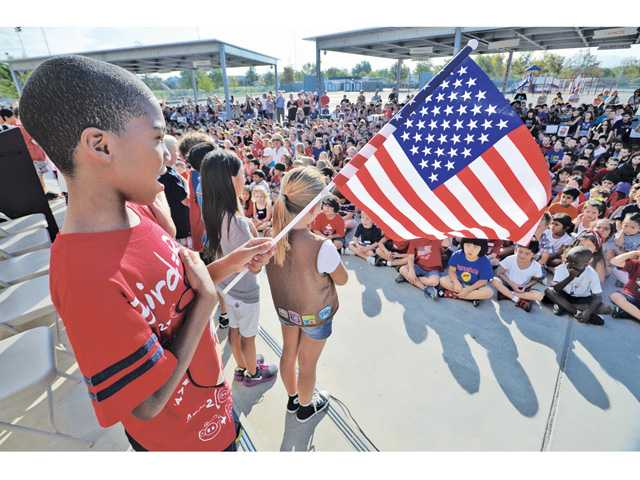 Jaden Clinkscales, 8, left, sings with his third-grade classmates at the Patriot Day ceremony held at Bridgeport Elementary School in Valencia on Tuesday.