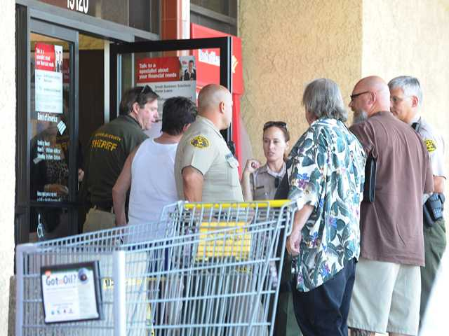 Sheriff's deputies and investigators question witnesses at the entrance of the Bank of America at 19120 Soledad Canyon Road in Canyon Country this morning.