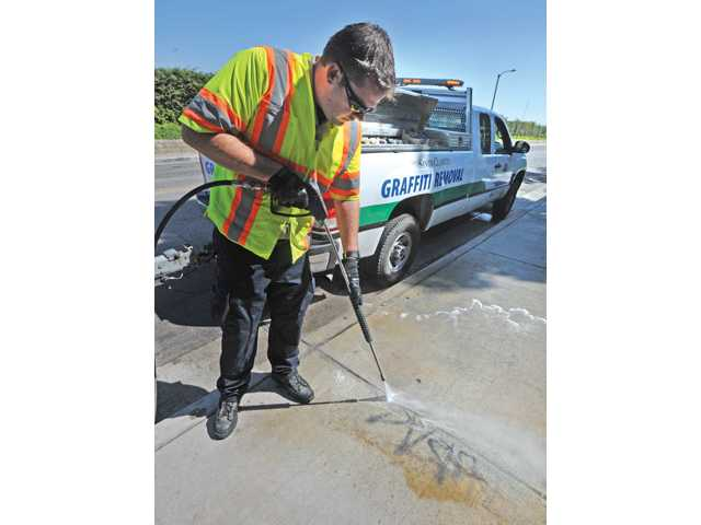 City of Santa Clarita Graffiti Removal Coordinator Justin Cummings uses a power washer to remove graffiti on the side walk on Sandy Drive in Canyon Country on Wednesday.