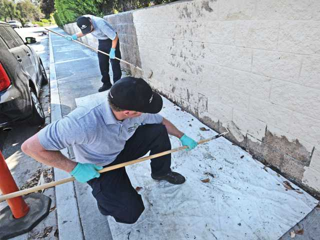 City of Santa Clarita Graffiti Removal team members Andrew Thompson, front, and Brandon Du paint the wall on Sandy Drive in Canyon Country on Wednesday.